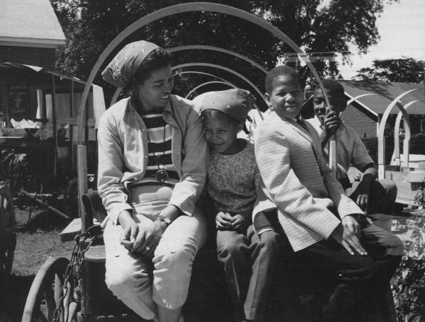 Joan Cashin, her daughter Sheryll, and two unidentified local boys wait to help waterproof the wagon covers in Grenada, Mississippi.