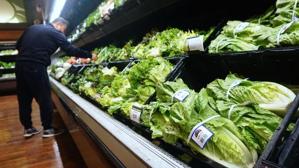 A man shops for vegetables beside romaine lettuce for sale at a supermarket in Los Angeles.