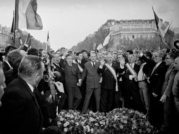 Hundreds of thousands of people, including finance minister Michel Debre and culture minister Andre Malraux (center, holding hands) demonstrated in support of President Charles de Gaulle on May 30.