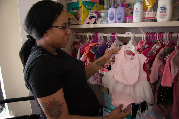 Taja Welton looks through the closet full of clothes for her unborn baby, Macen. At 37 weeks pregnant, Welton had to find a new OB-GYN because of the hospital closing in Kennett, Missouri.