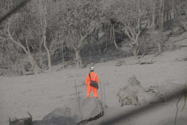 A firefighter is seen while he and other firefighters search for their missing colleague in the area affected by the volcanic eruption in Alotenango, Guatemala.