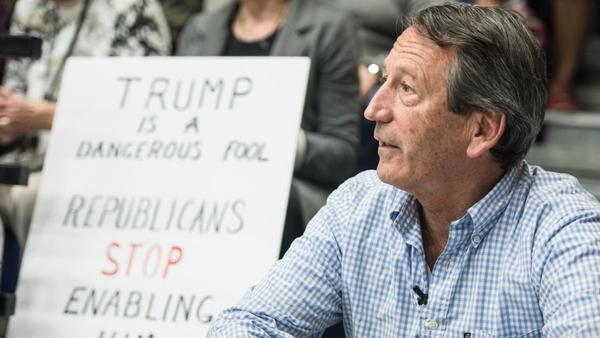 Rep. Mark Sanford, R-S.C., waits for his introduction during a town hall meeting last year in Hilton Head, S.C., in front of a sign from a protester.