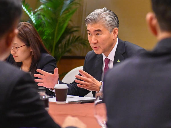In this photo released by the U.S. State Department, U.S. Ambassador to the Philippines Sung Kim talks with members of the North Korean delegation during a working group meeting on Monday in Singapore.