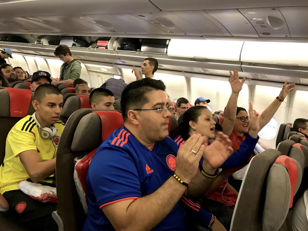 Soccer fans traveling from South America cheer after boarding a connecting red-eye flight from Madrid to Moscow.
