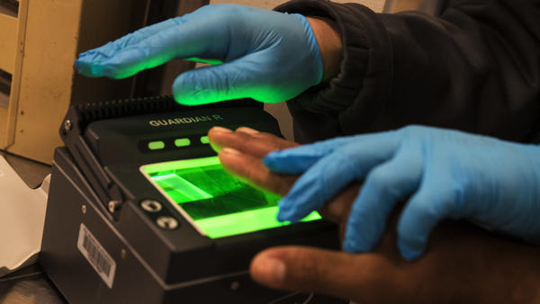 Immigration and Customs Enforcement agents take fingerprints while processing apprehended immigration fugitives inside the ICE staging facility in Los Angeles on April 18, 2017. Earlier this year ICE agents searching for an undocumented farmworker stopped his brother and sister-in-law. The couple sped off, crashed their car and died.