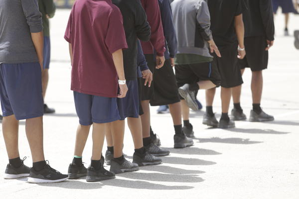 Boys 10 to 17 years old stand outside a government-contracted youth shelter in Brownsville, Texas. Ninety percent of the residents<strong> </strong>traveled to the United States alone seeking protection; the remainder were separated from their families at the border under a controversial new policy by the Trump administration.
