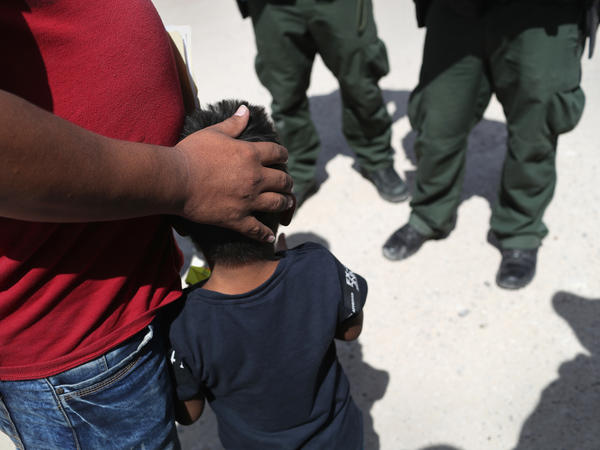 Border Patrol agents take a father and son from Honduras into custody near the U.S.-Mexico border. The asylum seekers were then sent to a U.S. Customs and Border Protection processing center for possible separation.