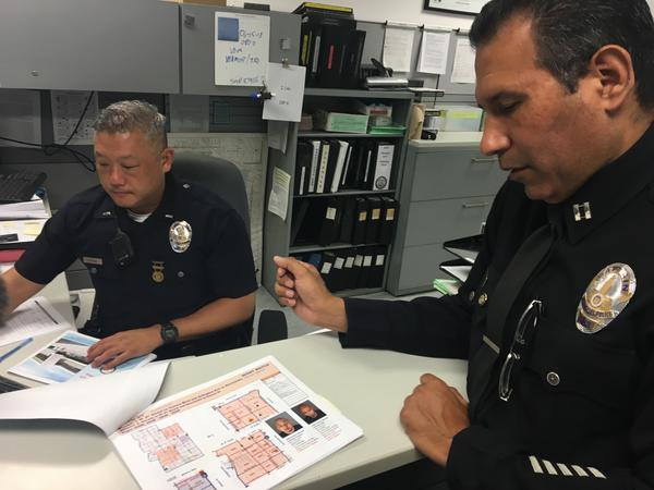 "Lt. James Hwang and Capt. Alex Vargas review the ""mission sheet"" for officers patrolling the Olympic Division. It's generated with various analytics tools, and points patrol officers toward certain neighborhoods and people."