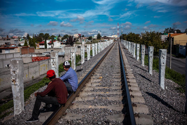 "Two Central American migrants rest on the railway through which <em>La Bestia</em> crosses near the Sagrada Familia shelter. Migrants risk the danger of jumping the train ""because they're fleeing poverty and have to make this journey with practically no money,"" says Sergio Luna, the director of the shelter."