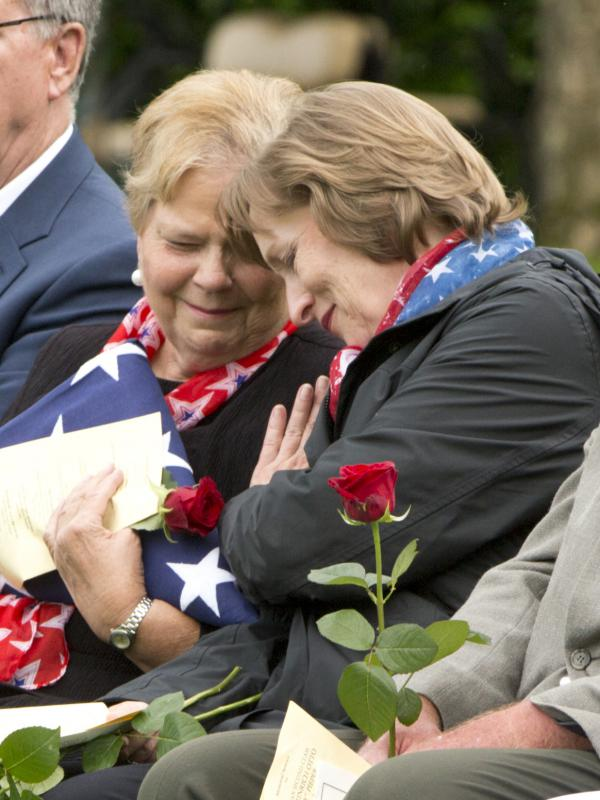 Family members of the Pieper twins, Linda Suitor (left) and Susan Lawrence, hug during a reburial service for their uncle at the Normandy American Cemetery.