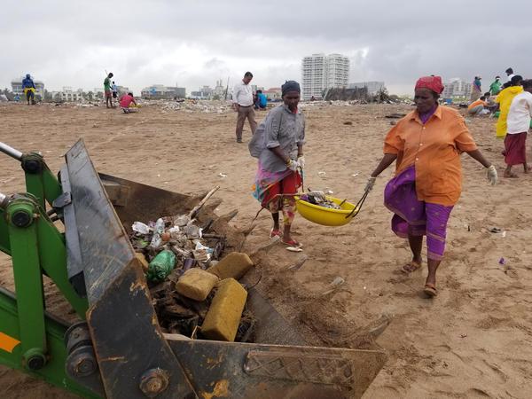 At Mumbai's Versova Beach, dozens of volunteers show up several times a week to rake up trash.