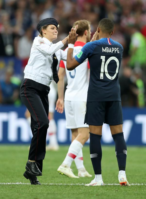 A pitch invader high fives Kylian Mbappe of France during the 2018 FIFA World Cup Final between France and Croatia.