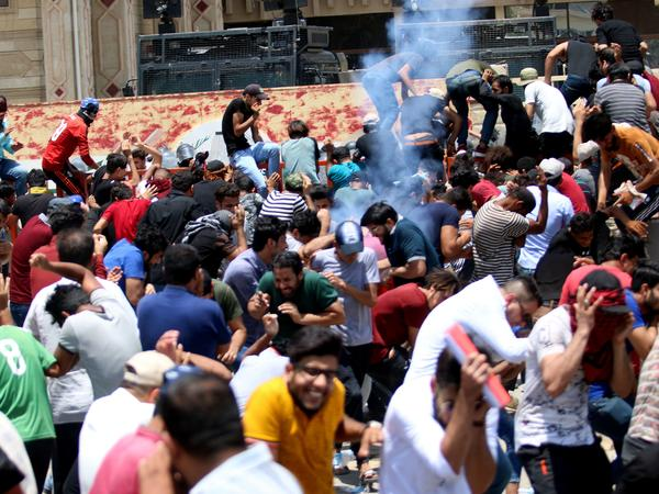 Protesters duck as Iraqi security forces fire tear gas during a demonstration against unemployment and a lack of basic services in the southern Iraqi city of Basra on Sunday.