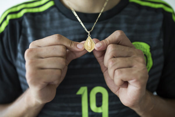 Ricardo Osuna, who graduated from Galax High School this spring, holds a Virgin Mary necklace that he wears. Osuna helped to lead the school's soccer team to the state championship title the past two years.