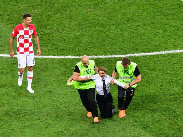 A member of the Russian protest-art group Pussy Riot is escorted by stewards during the Russia 2018 World Cup final match between France and Croatia.