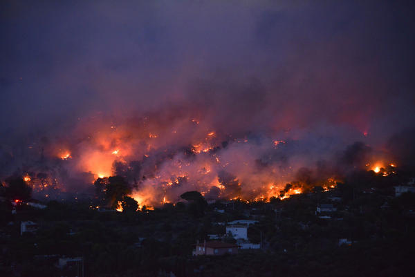 Flames rise as a wildfire burns in the town of Rafina, near Athens, on Monday.