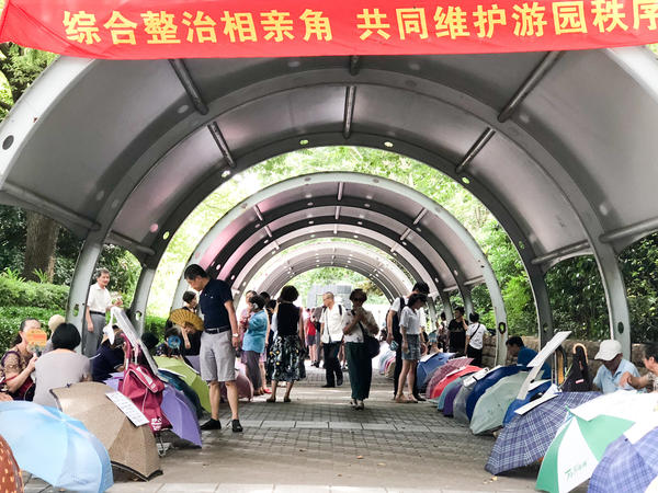 "At Shanghai's weekly ""marriage market,"" parents advertise their unmarried adult children with signs taped to umbrellas. Chinese parents and the government are doing what they can to reverse the trend of falling marriage rates. The sign above the entrance reads: ""Comprehensively manage the marriage market, maintain the order of the park together."""