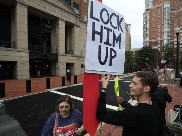 Gayelynn Taxey and Danny Hastings protest in front of the federal courthouse in Alexandria, Va., Tuesday.
