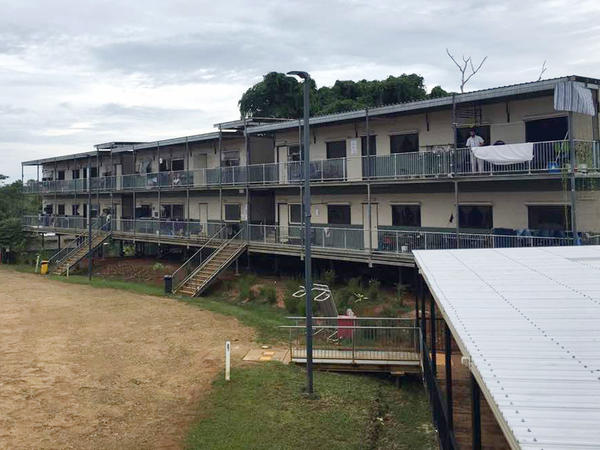In this July 17 photo provided by Aziz Abdul, a man standing on a balcony at the East Lorengau Refugee Transit Center on Manus Island, Papua New Guinea. The question of what will become of the hundreds of asylum-seekers banished by Australia to sweltering immigration camps in the poor Pacific island nations of Papua New Guinea and Nauru has become more pressing.