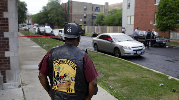 A bystander watches as Chicago police investigates a street where multiple people were shot on Sunday in Chicago.