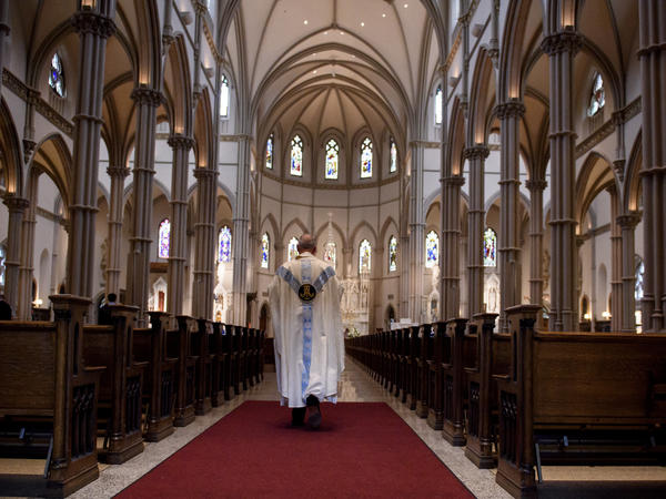 Father Kris Stubna walks to the sanctuary following a mass at St. Paul Cathedral, the mother church of the Pittsburgh Diocese, last week.
