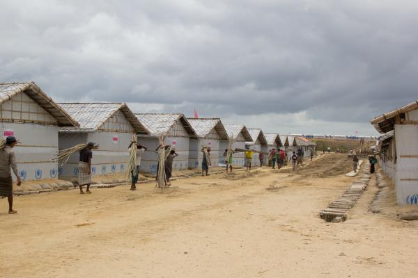 Workers carry bamboo poles past newly constructed shelters at the Camp 4 Extension. The U.N. refugee agency is moving Rohingya refugees to this new area to get them away from hazardous conditions in the old camps.