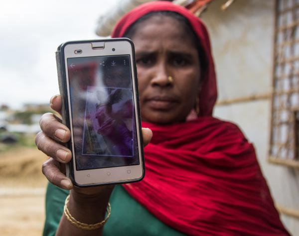 Rohingya refugee Roshedha Begum, 40, holds up a photo of her son's dead body. He was killed, she says, by Myanmar soldiers during the violence last year that drove more than 700,000 Rohingya into Bangladesh.