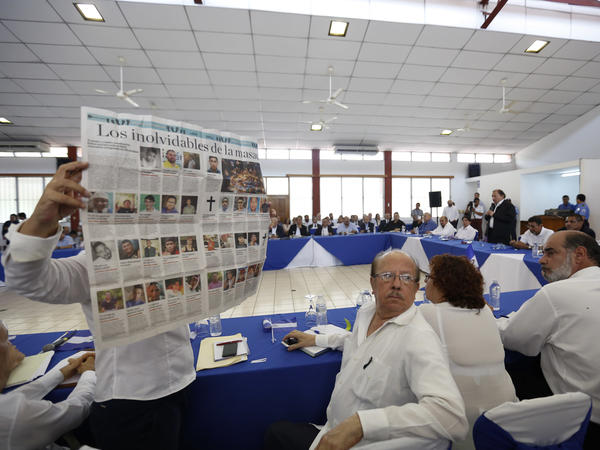 A woman holds up a Nicaraguan newspaper that published images of some of the people who have died in recent protests there, interrupting Nicaraguan President Daniel Ortega at the opening of a dialogue between the government and opposition and civic groups in Managua, on May 16.