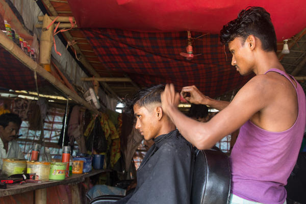 In the Balukhali 2 refugee camp, three young men have set up a barbershop under a tarp. They picked up their barber skills by trimming each other's hair when they couldn't afford a professional cut.