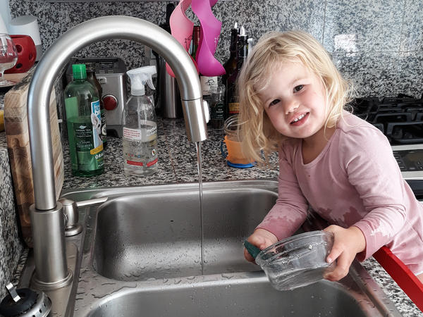 Rosy does dishes. Getting the 2-year-old involved in chores did lead to the kitchen being flooded and dishes being broken. But now she is still eager to help.