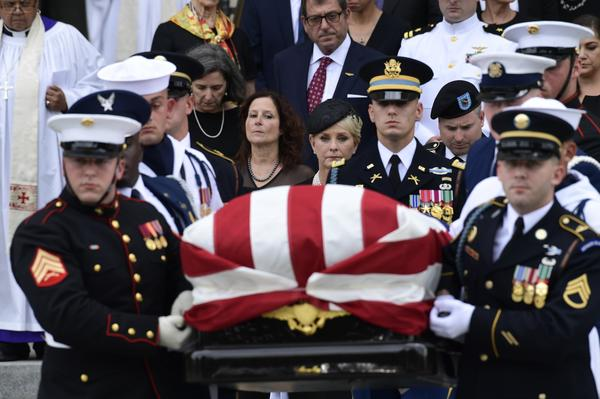 The casket of Sen. John McCain, R-Ariz., is carried out of the Washington National Cathedral in Washington, Saturday, after a memorial service, as Cindy McCain is escorted by her son Jimmy McCain and other family members.