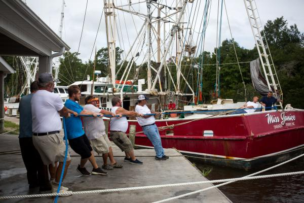 Crew members and boat owners help moor the Miss Janice, a shrimp boat, to the dock at Mitchell Seafood on Wheeler Creek in Sneads Ferry, N.C., on Thursday.