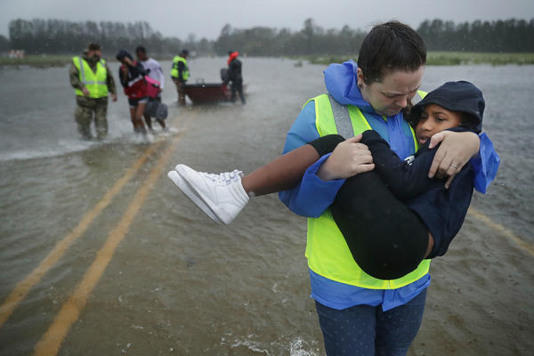Volunteer Amber Hersel from the Civilian Crisis Response Team helps rescue Keiyana Cromartie, 7, and her family from their flooded home on Friday in James City, N.C., near New Bern.
