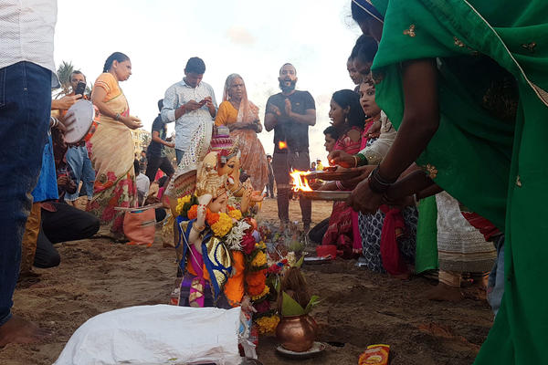 Faithful place their idols in the sand, light incense and make offerings to Lord Ganesha, before carrying the statues down to the water to immerse them.