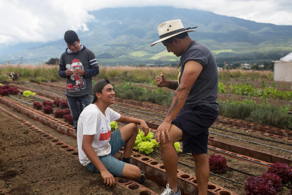 Juan Pablo Romero (right), founder and director of Los Patojos, talks with current student Christopher Alvarado, who participates in the construction and maintenance of the new campus during the mornings in Jocotenango, Guatemala.