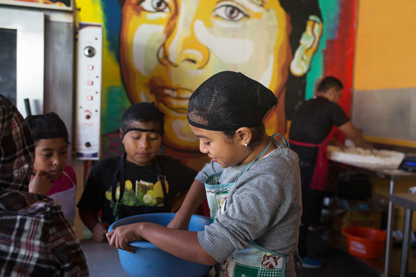 Fourth graders prep dough to bake during a cooking class. Los Patojos has grown into a community center and school educating over 300 students.