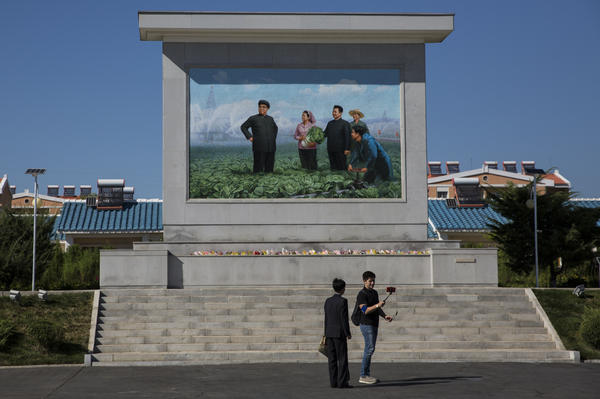 A Russian journalist uses a selfie stick to record a stand-up at a collective farm in Pyongyang, as his government-provided guide watches. Mosaics like this are found throughout the country and commemorate visits by North Korean leaders.