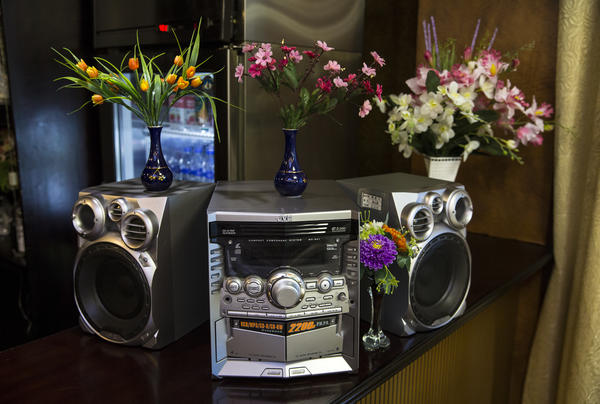 A Japanese-made stereo system, adorned with flowers, sits on a bar at a restaurant in Pyongyang