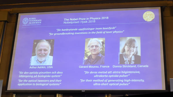 A screen displays portraits of Arthur Ashkin of the United States, Gérard Mourou of France and Donna Strickland of Canada, who won the 2018 Nobel Prize in Physics, at the Royal Swedish Academy of Sciences on Tuesday in Stockholm.