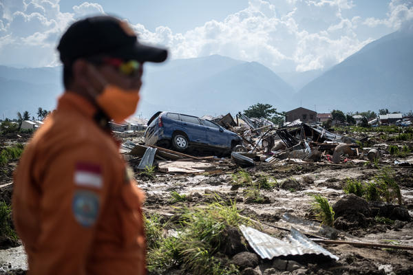A search-and-rescue team member scans the ruins of an area in Palu, on the Indonesian island of Sulawesi on Thursday. Of the more than 1,500 people who died in the disaster, authorities say more than 1,200 lived in Palu.