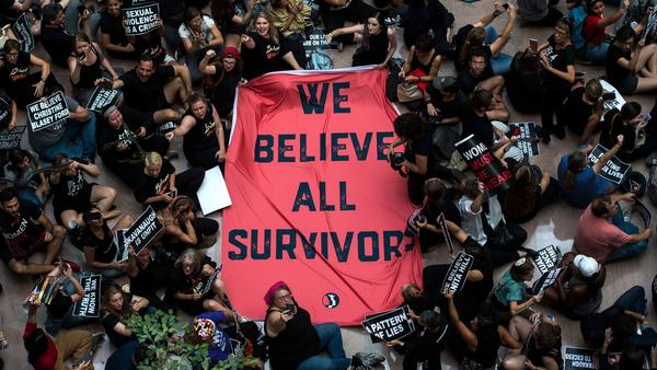 "Protesters unfurl a sign reading, ""We believe all survivors,"" as they occupy the Hart Senate Office Building Thursday during a rally against Kavanaugh."