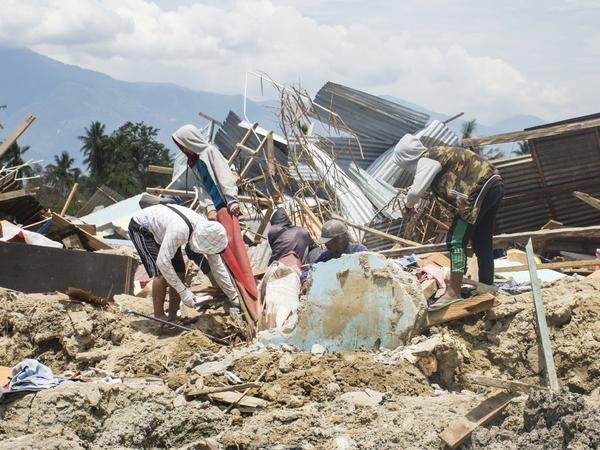 Residents of Petobo sift through debris to salvage what they can in the aftermath of the earthquake and tsunami disaster that struck the Indonesian island of Sulawesi on Sept. 28. Petobo lies in Palu city, and the neighborhood is thought to contain so many dead bodies that the government is considering halting recovery efforts and declaring it a mass grave.