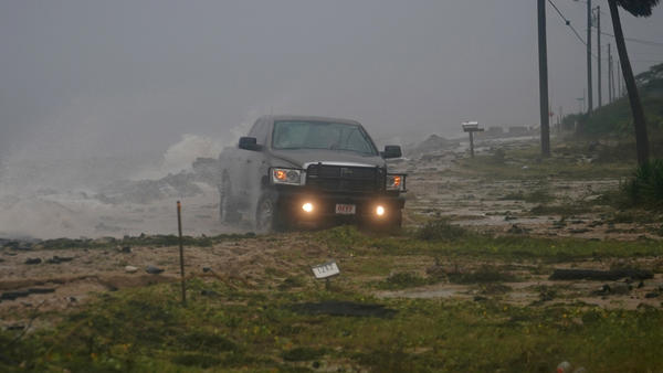 A truck drives along a washed-out road as Hurricane Michael's storm surge and winds come ashore in Alligator Point, Fla., Wednesday.