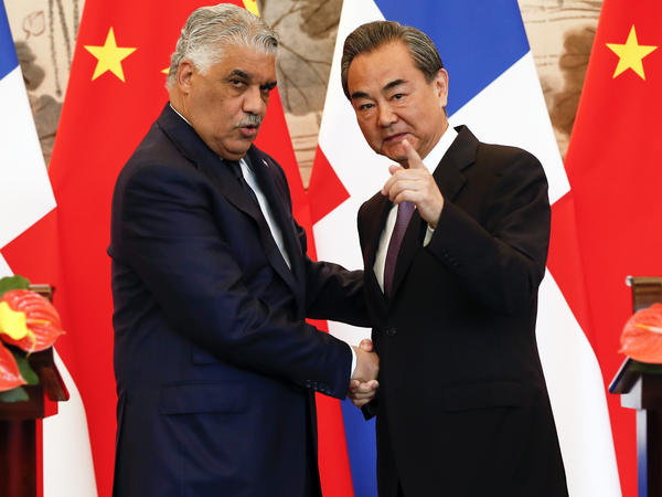 Chinese Foreign Minister Wang Yi (right) shakes hands with his counterpart from the Dominican Republic, Miguel Vargas, during a signing ceremony on May 1 in Beijing.