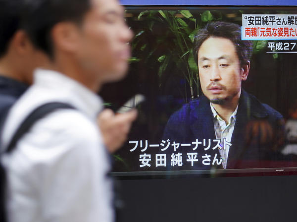 Men walk past a TV screen showing a news program with an image of Japanese freelance journalist Jumpei Yasuda, on Wednesday. Yasuda, who disappeared three years ago in Syria, has been released and is now in Turkey, a Japanese official said.