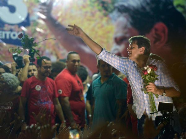Fernando Haddad, Bolsonaro's opponent, throws flowers to supporters during a rally in Recife on Thursday.