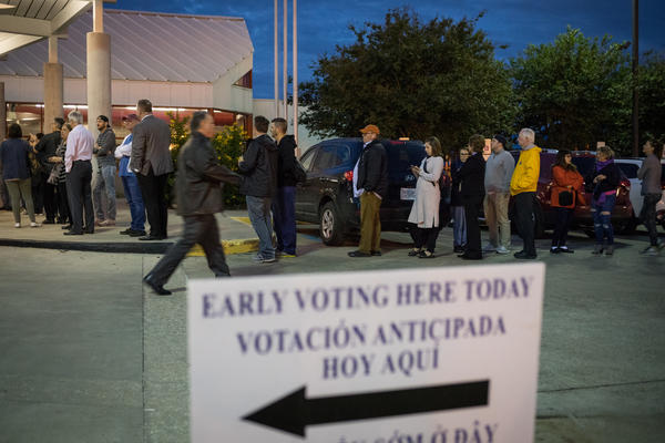 People wait in line to vote at a polling place on the first day of early voting on Oct. 22 in Houston. Texas Attorney General Ken Paxton has been aggressively prosecuting people for voting violations, which critics argue is designed to intimidate non-white voters.