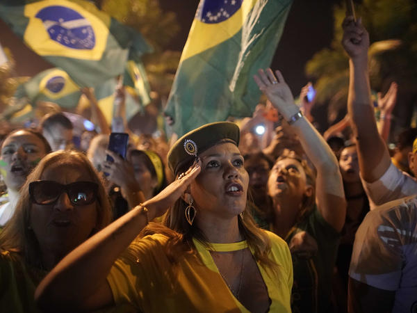 A supporter of Jair Bolsonaro salutes during a celebration in front of his residence after he was declared the winner of the election runoff, in Rio de Janeiro, on Sunday.