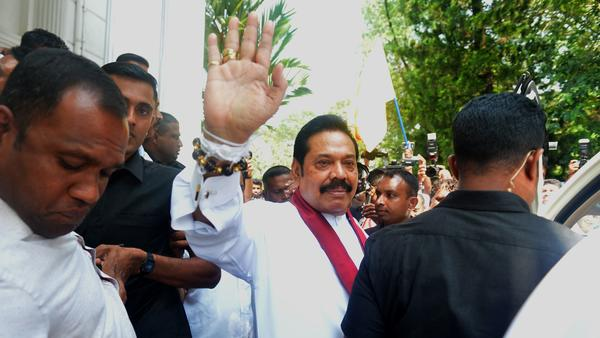 Sri Lanka's newly appointed prime minister, Mahinda Rajapaksa, waves to supporters Monday in the capital, Colombo. The man he intends replace, Ranil Wickremesinghe, demanded that lawmakers be allowed to end his standoff with the country's president.