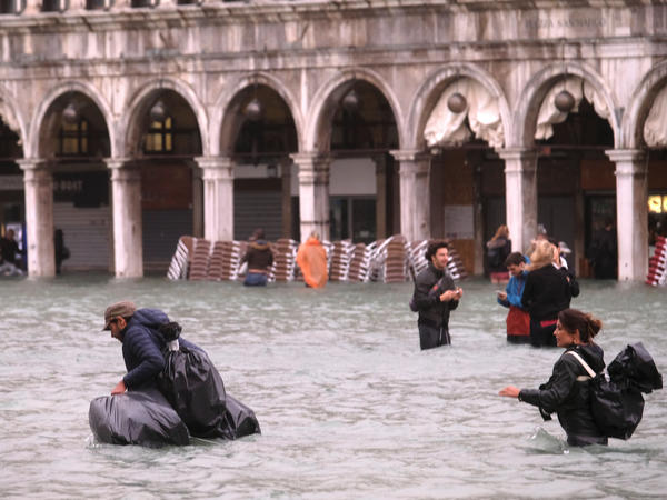 People walk in a flooded Saint Mark Square in Venice, Italy.